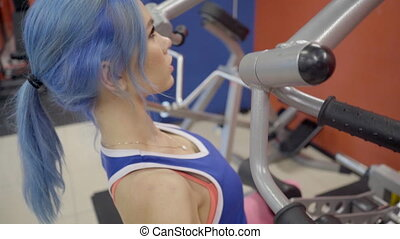 The portrait of female with blue hair who does chin-ups on...