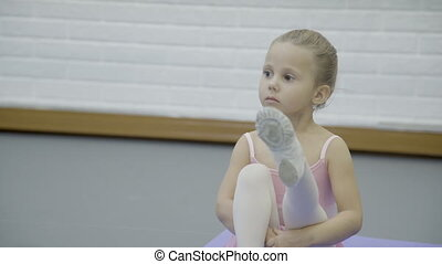 The portrait of girl who sits on the mat and stretch her...