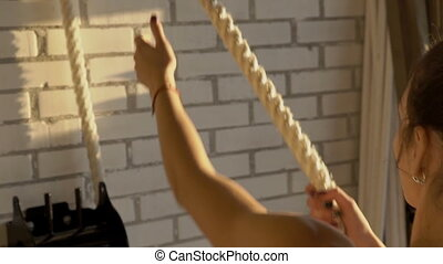 The portrait of young woman who pulls the rope in the gym near the white wall.