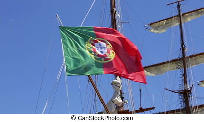 The Portuguese flag on a sailing ship at sea. In the wind. -...