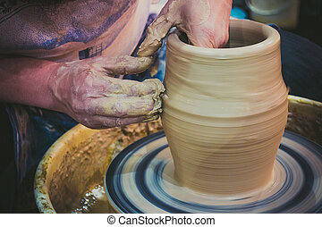 The potter molds clay jug pot closeup