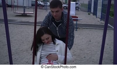 the pregnant girl with the guy in the evening on the swing