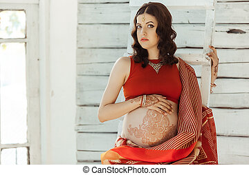 The pregnant woman belly with henna tattoo - Indian picture...