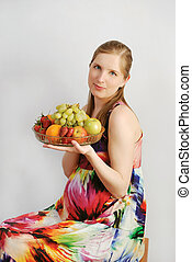 The pregnant young woman with a dish of fruit
