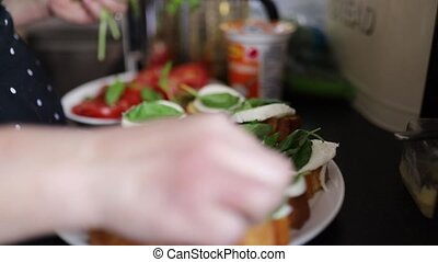 FHD Video of the hands of a person adding fresh green leaves to a bread and cheese dish