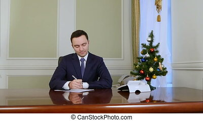 The president signing documents by the desk in office. ...