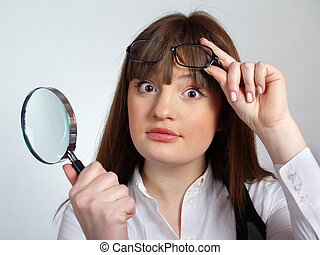 The pretty young woman with a magnifier in her hand