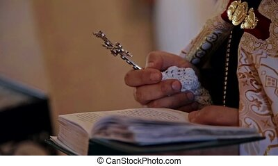 The priest holds a cross and reads a line from the Bible