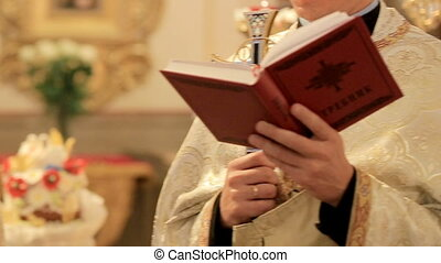 The priest read a prayer from the book. Church rite