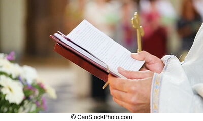 The priest reads the Bible