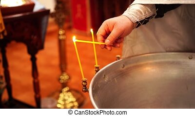 The priest's hand lights candles on the font in the Orthodox church during baptism. Christian religious traditions.