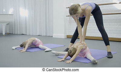 The prima ballerina teaches her little students how to do middle leg split correctly.