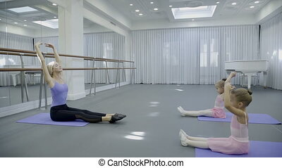 The prima ballerina teaches two children how to strench the...