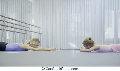 The prima ballerina teaches two girls to do back exersices...