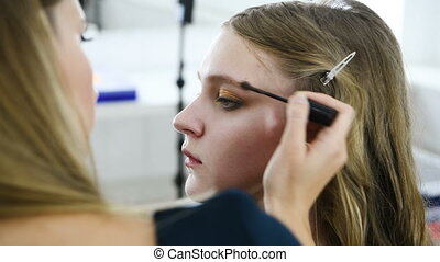 The process of applying makeup to the face model. Powder,...