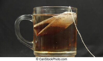 The process of brewing tea bags in a glass of hot water.