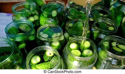 the process of canning pickled gherkins for the winter, pickles cucumbers in glass jars.