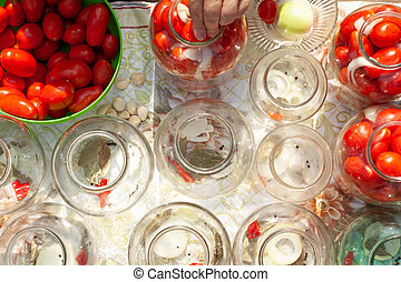 the process of canning pickles tomatoes. grandmother lays tomatoes in a jar