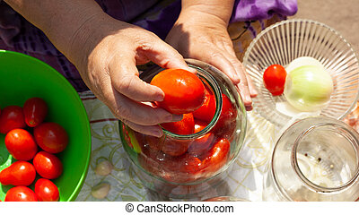 the process of canning pickles tomatoes. put tomatoes in a jar