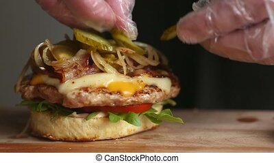 The process of cooking big Burger is a professional chef, close-up. Puts cucumbers with cheese on a bun