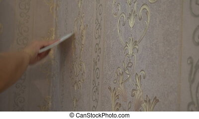 the process of gluing Wallpaper on the wall,the hand of the worker to smooth the Wallpaper with a spatula clamping