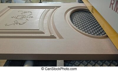 the process of grinding wooden doors on the machine. production of interior doors of wood