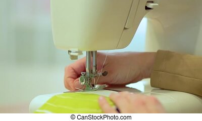 The process of hemming curtain edges from white mesh fabric.