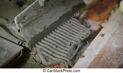 the process of leveling the cement with a spatula, the...