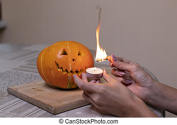 the process of making a Halloween pumpkin. light a match and candle. horror theme and Hallowe'en