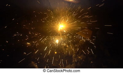 The process of manufacturing a decorative metal product. Metal sparks fly apart from the detail. Welding of metal in the process of creating decorative metal products.