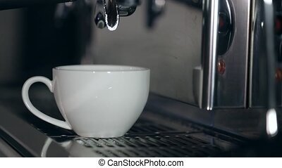 The process of preparation of cappuccino. Coffee is poured into a white cup.