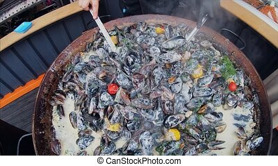 The process of preparing mussels in a large saucepan.