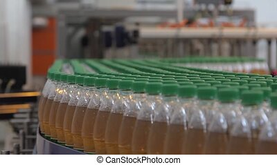 The production line of lemonade. A conveyor of plastic bottles filled with liquid.