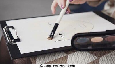 The professional makeup artist paints a face chart on watercolor paper using palette shades for cosmetics and brush. Female artist in a dress paints a painting on canvas at home