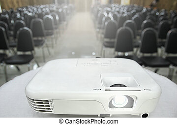 The projector is placed on a table covered with a white cloth placed in front of the meeting room