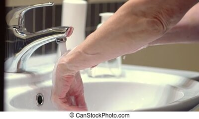 The proper hand hygiene technique protects against coronoviruses and germs. Prolonged rinsing with water is mandatory after soaping and rubbing hands. Close up view.