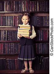 the pursuit of knowledge - Pretty little girl holds a stack...