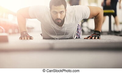 The Pushup Workout - Bearded man in white t-shirt doing...