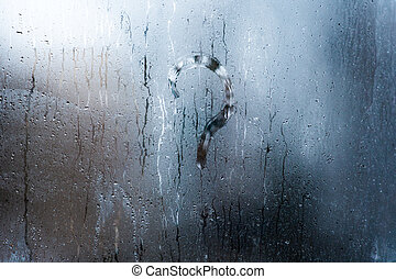 the question mark on the wet window glass