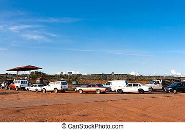 The queue of cars at gas station - Cars wait in long line to...