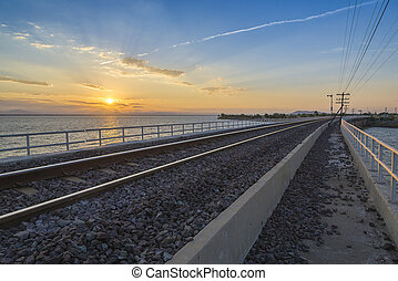 the railway or railroad crossing the lake with the sunrise at the morning