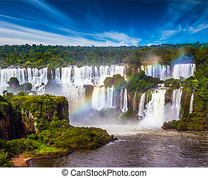 Several waterfalls from Iguazu Falls. Powerful two-stage waterfall creates a watery dust and a rainbow. The concept of exotic and extreme tourism