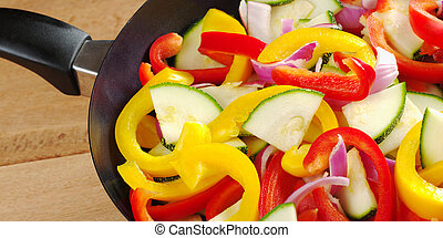 The raw ingredients of ratatouille in a frying pan. Ratatouille is a light summer French dish which mainly consists of zucchini, pepper and onions, but there are many variations to it (Selective Focus