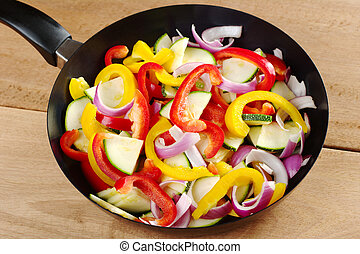 The raw ingredients of ratatouille in a frying pan. Ratatouille is a French light summer dish which mainly consists of zucchini, pepper and onions, but there are many variations to it (Selective Focus