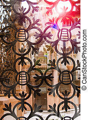 The rays of sun through forged lattice fence Scaliger Tombs in