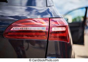 The rear headlight of a black sports car