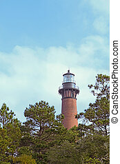 The red brick structure of the Currituck Beach Lighthouse rises over pine trees at Currituck Heritage Park near Corolla, North Carolina