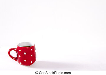 The red cup in a white point is on a white wooden table. Copy space