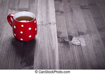 the Red cup in a white point is on a white wooden table. Paper hearts hang on the wall