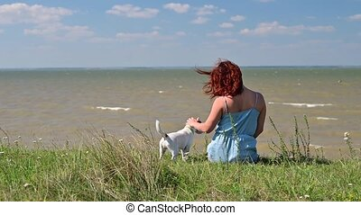 The red-haired woman and the dog are sitting on the seashore.